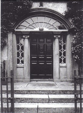 Photo:Round headed arched door opening encasine stone doorcase with radial fanlight and timber raised and fielded panelled door.