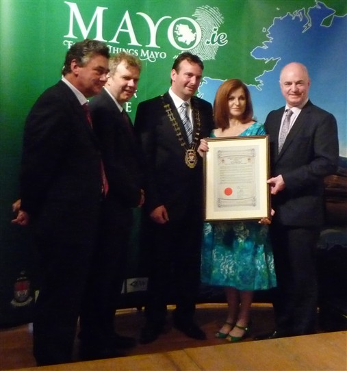 Photo:Maureen Dowd being presented with a framed parchment by newly elected Mayo County Council Cathaoirleach, Cllr. Cyril Burke.  Also from L to R Mr. John Condon, County Secretary, Mr. Niall O'Dowd and Mr. Peter Hynes, County Manager