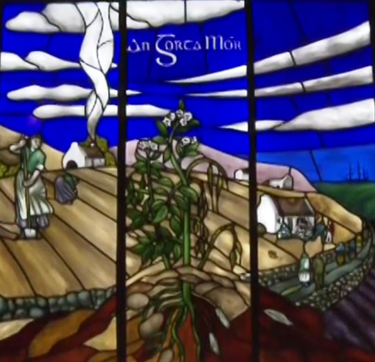 Photo:Stained-glass panel from the Museum. Notice the single storey cottages, the stone walls, the potato ridges, the woman digger and the potato plant.
